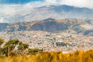 Andes range mountains landscape scene from the top of Cruz Loma hill and cityscape of Quito, Ecuador